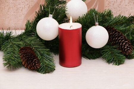 Red burning candle with Christmas tree decorations on the background of a fir branch.