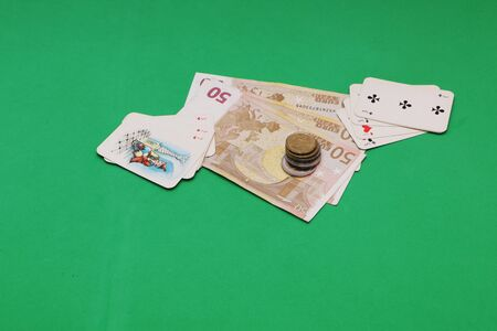 In the casino on the gaming table are cards and money. The background is green.
