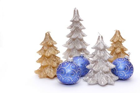 Christmas trees in the form of candles with blue balls to decorate the Christmas tree. The background is white. Foto de archivo