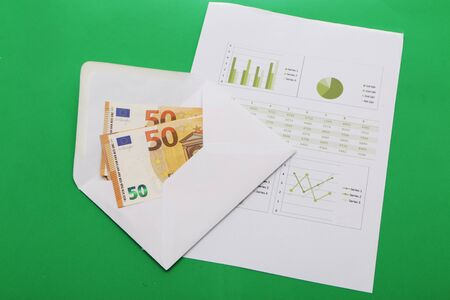 Business papers, contract and envelope with money on a green background.