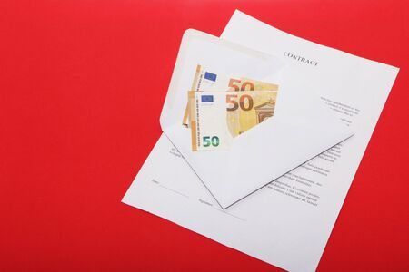 Business papers, contract and envelope with money on a red background.