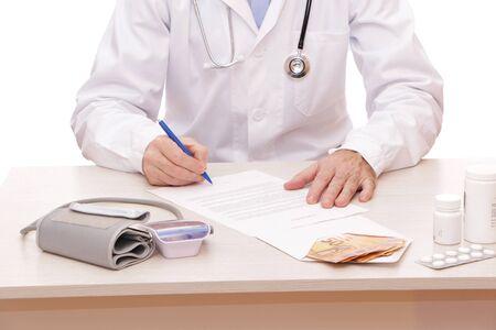 El médico firma un contrato con el paciente. Sobre la mesa hay un dinero, un instrumento médico, un estetoscopio, un dispositivo médico para medir la presión para escuchar los pulmones y el corazón de un paciente con auriculares sobre un fondo blanco.