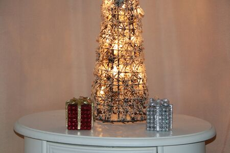 A tree of shattered glass is illuminated by light bulbs. Near the table are gift boxes for jewelry.
