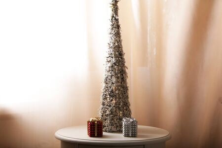 A tree of shattered glass is illuminated by light bulbs. Near the table are gift boxes for jewelry. Stock Photo