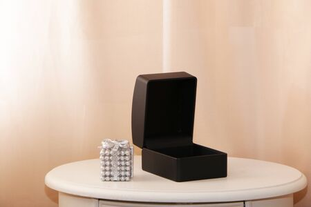 Black gift box for jewelry on a white table. Pink background.