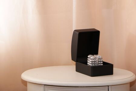 Black gift box for jewelry on a white table. Pink background. Stock Photo