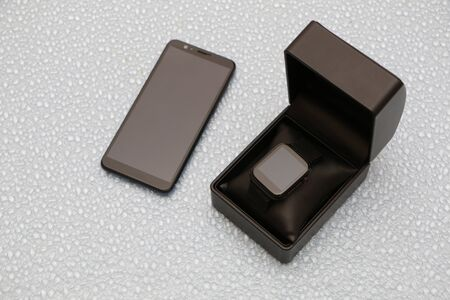 Smartphone and smartwatch in a black gift box on a blue background in the form of drops of water.