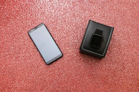 Smartphone and smartwatch in a black gift box on a tap with a granite background in the form of water drops.