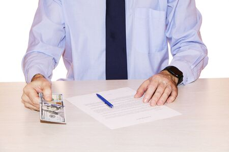 A businessman signs a contract and issues cash dollars and euros in an envelope.
