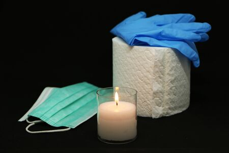 Close-up - a memory candle against the background of a disposable medical mask, rubber gloves and toilet paper.