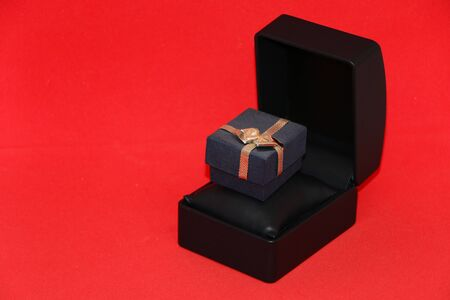 Black gift box for jewelry on a display case. Bright red background