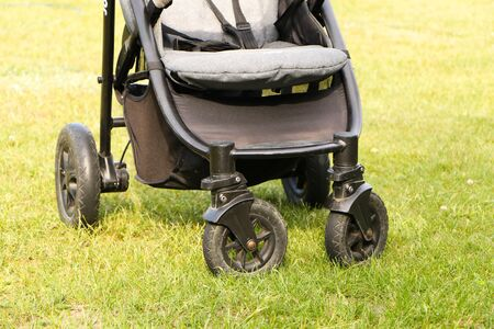 Black baby stroller stands on the green grass. Banco de Imagens