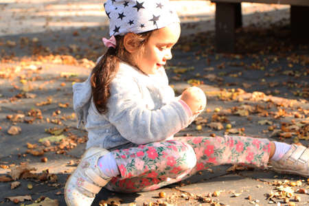 Girl in bright fashionable clothes collects chestnuts in the autumn park. Happy little child. The girl laughs and plays in the autumn in the park.