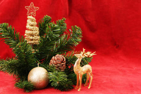 Christmas and New Year gifts as a symbol of New Year and Christmas. Festive decorations for the new year and christmas. Christmas festive decor with tree, candle, gifts on a red background.