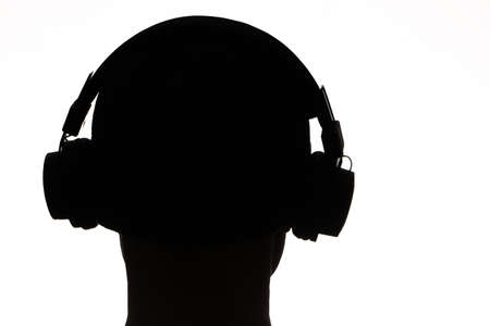 Wireless technology - Dark male silhouette with headphones on a white background. Dark silhouette in headphones listens to music on a white background.