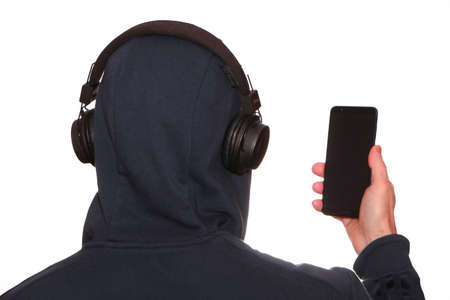 A man in a sports jacket with a hood on his head listens to music with headphones on his smartphone. Modern technologies - a smartphone in hand and a wireless earpiece on the head. Distance education.