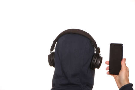 A man in a sports jacket with a hood on his head listens to music with headphones on his smartphone. Modern technologies - a smartphone in hand and a wireless earpiece on the head. Distance education. 版權商用圖片