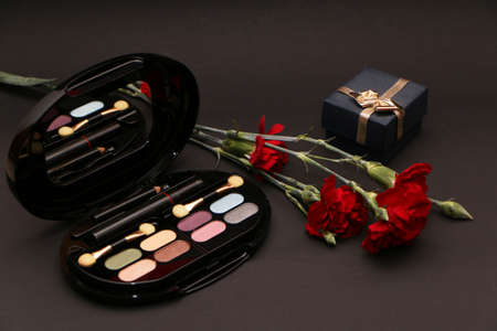 Perfume set on a wooden table is decorated with a bouquet of carnations. The background is black. Beautiful perfume bottle and female makeup on the background of a bouquet of carnations.