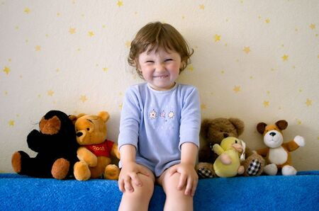 Small girl with funny smile sitting on sofa with plush soft toy animals. The Pooh, Keeper Stock Photo - 857531