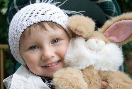 Small smiling girl with plush rabbit toy. Girl in white knit cap.  Picture taken in early autumn. Stock Photo - 857536