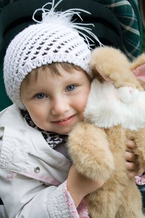 Small smiling girl with plush rabbit toy. Girl in white knit cap.  Picture taken in early autumn. Stock Photo - 857537