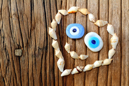Creative shape of heart with sea shell and amulet smiling on a wooden table backround Stok Fotoğraf
