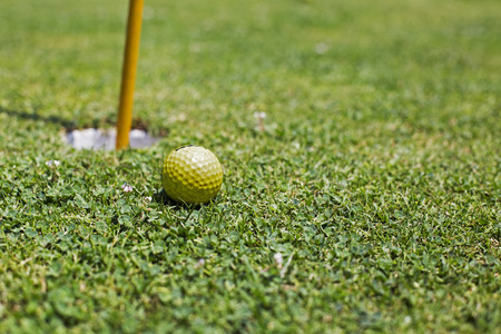 Golf Ball Near the Hole on the Green Grass photo