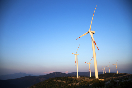 Wind energy turbines are on the mountain and produce cleanest electric energy photo