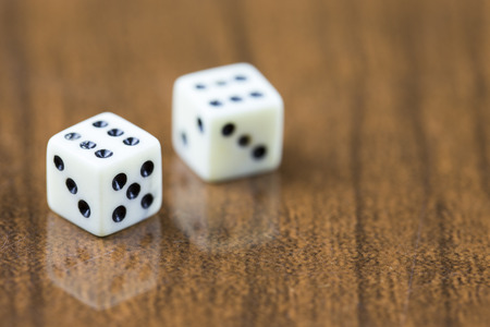 double the chances: Two dice on a wooden background showing two sixes