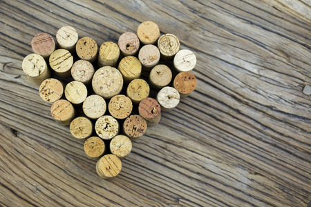 Wine corks form a heart shape image on the wood board background