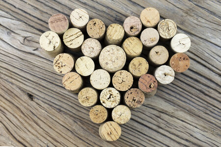 Wine corks form a heart shape image on the middle of wood board background photo