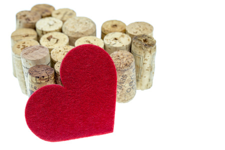 Red textile heart with wine corks form a heart shape on isolated white background photo