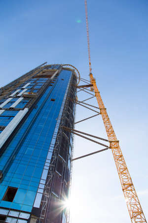 new building construction: Huge crane rising near construction of a skyscraper