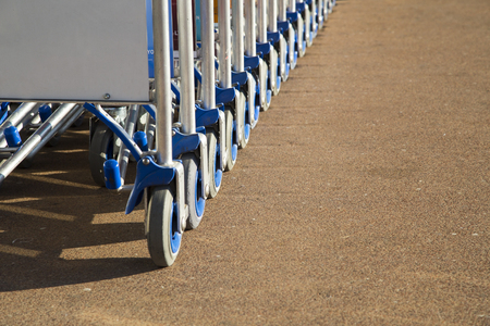 Row of luggage carts with advertisement space closeup view photo