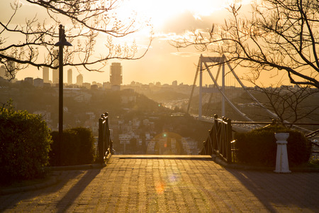 Modern side of Istanbul and Fatih Sultan Mehmet Bridge retro view from high angle at sunset golden hours. Behind steps of a park with back light image have a vintage effect with no people photo
