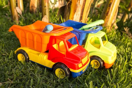 symbolize: Colorful plastic toy trucks in the grass to symbolize construction and carrying trade business Stock Photo