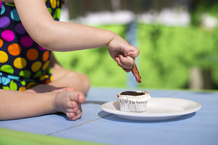 smudgy: Cute baby wearing spotted swimsuit tasting a cupcake with her finger