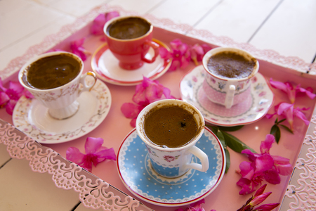 foamy: Four small cups of traditional foamy Turkish Coffee serving on a colorful flowery pink tray on top of a white wooden table in low angle view
