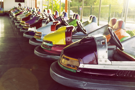 Long row of colorful bumper cars parked in an amusement park 스톡 콘텐츠