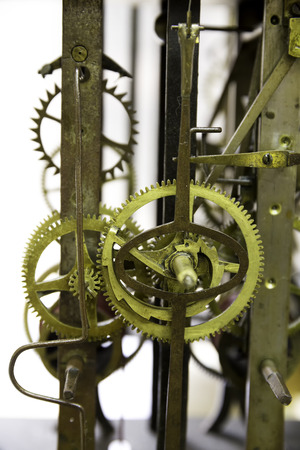 greasy: Close up view of greasy and rusty old wall clock mechanism with gears, isolated on white background Stock Photo