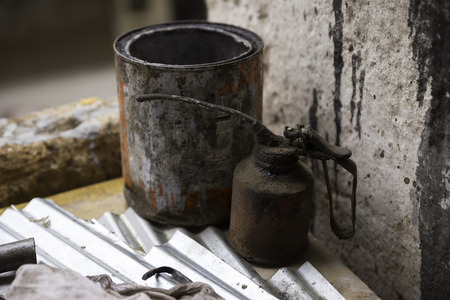 lubricate: Old dirty greasy lubricator and paint box on the table in a working area Stock Photo