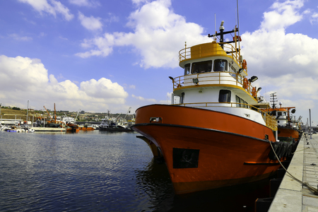 Red colored fishing boat in a commercial harbor and a blue sky