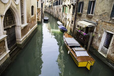 View of the Rio di San Cassiano Canal with boats and colorful facades of old medieval houses in Venice Italy