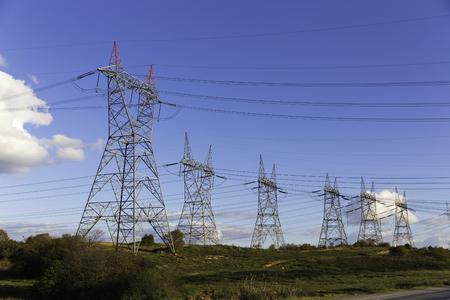 Lots of high voltage power transmission towers with blue sky background