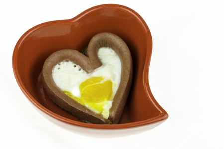 Egg with a heart-shaped sausages in red heart-shaped plate on isolated white background