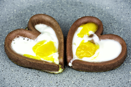 Couple of eggs cooking with heart-shaped sausages in frying pan. Cooking fried egg in the form of heart.