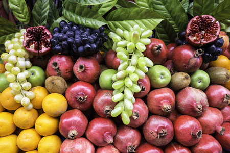 Many kind of different fruits on a showcase closeup view. Street vendor selling colorful exotic fruits and fruit juice.