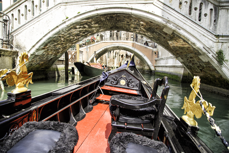 View from gondola trip during the ride through the narrow canals with many bridges in Venice Italy