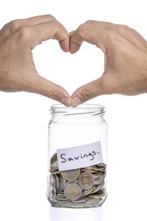 penny pinching: Heart sign on the jar savings. Stock Photo