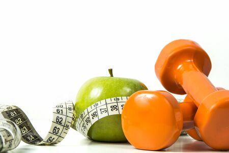 pesas: Manzana verde, cinta métrica y las pesas en el fondo aislado. Foto de archivo
